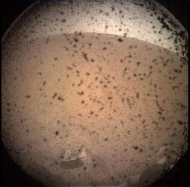 Erste Aufnahme von der Marsoberfläche aufgenommen durch staubverdreckte Linsenabdeckung. © NASA/JPL-Caltech